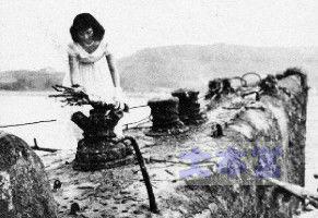 引上げた伊33潜で花を手向ける女性